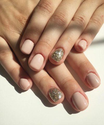 mani e piedi di donna con unghie corte nude e glitter