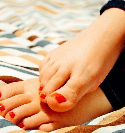 piedi di donna con unghie corte colorate